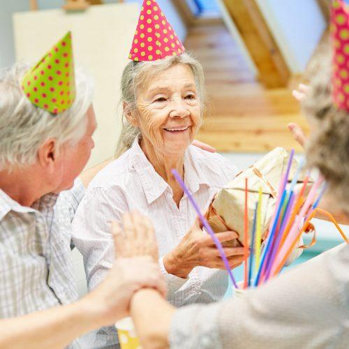 Senior Frau als Geburtstagskind freut sich über ein Geschenk auf ihrer Party